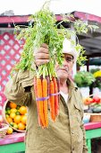 A farmer holding a bunch of carrots in assorted colours
