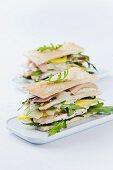 Clubsandwich aus gerösteten Tramezzini, Rucola, Hähnchen, Parmaschinken, Mango, Parmesan und Majonäse