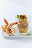 Colourful vegetable spaghetti made from kohlrabi, carrots, radish and cucumber, with fried king prawns