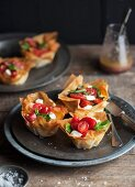 Filo pastry tartlets with caprese (tomatoes, basil and mozzarella)