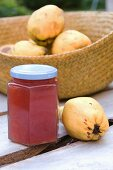 A jar of quince jelly and fresh quinces