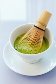 Matcha in a bowl with a bamboo whisk