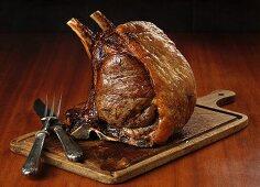 Roast rack of beef on a chopping board