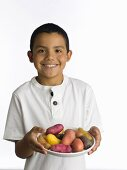 A Young Boy with a Plate of Raw Potatoes