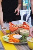 People by a buffet table set with a bread basket, a plate of crudités, and dips