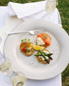 Plate of potato pancakes with creme fraiche, salmon roe and asparagus