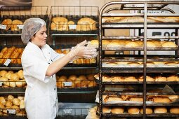 Young sales assistant with trays of bread