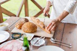 Woman cutting baguette