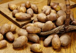 Fresh potatoes of the variety 'Golden Wonder' in a basket and on a chopping board