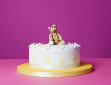 A teddy bear cake with sugar flowers