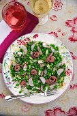 Pea salad with radishes and roast beef rolls