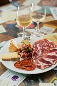 An appetiser platter with cold cuts, cheese and capers