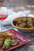 A Bowl of Seafood Stew with a Glass of Wine and a Plate of Toasted Bread