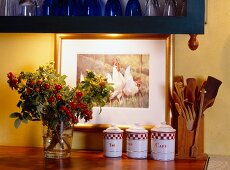 A detail from the kitchen, with storage jars, kitchen utensils and sprigs of rosehips in front of a picture of chickens