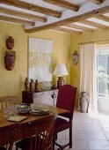 A dining room in an English country house with a wooden table and pieces of art from Nepal and Tibet