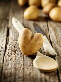 Heart-shaped potato, a wooden spoon and a knife on a wooden surface