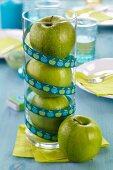 Grüne Äpfel in Glas gestapelt als Tischdekoration