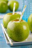 Grüne Äpfel als Trinkgefäße mit Strohhalm