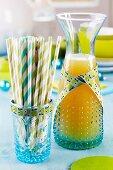 Karaffe mit Apfelsaft und Glas mit Strohhalmen, verziert mit Dekoband