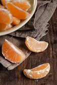 Peeled clementine segments in and in front of a bowl
