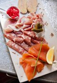 A platter of sausage with salmon, goose liver and pickled gherkins (Italy)
