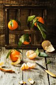 Fresh tangerines with leaves on old wooden table