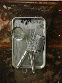 Assorted kitchen utensils on a metal tray