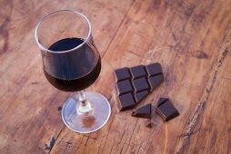 Stillleben mit Bitterschokolade & Glas Rotwein