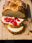 Hefezopf (sweet bread from southern Germany), partly sliced with butter and jam