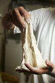 A baker pulling bread dough apart