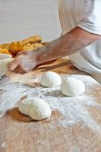 Bread dough and white loaves on a floured wooden table