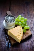 Various types of cheese on a wooden board with green grapes