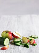 A still life featuring cucumber, apple and mint