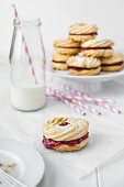 Jam biscuits with a small bottle of milk and pink straws.
