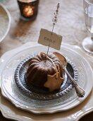 Kleiner Schokokuchen mit Namensschild auf weihnachtlich gedecktem Tisch