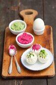 Boiled eggs with three dips: beetroot dip, horseradish dip and pea dip