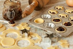 Mini mince pies being decorated with star-shaped lids in the baking tin