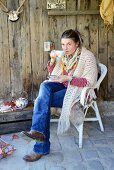 Late summer tea break snuggled in hand-made poncho on shabby-chic veranda with vintage crockery and rustic ornaments