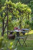 Runder Gartentisch mit Stuhl in sommerlichem Garten; darauf eine Kristallschale mit frisch gepflückten Erdbeeren