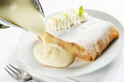 Apple and quark strudel with whipped cream and vanilla sauce