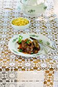 Venison goulash with mushrooms and Spätzle (soft egg noodles from Swabia) on a lace tablecloth