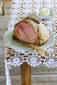 A sliced ham wrapped in bread served with creamy horseradish