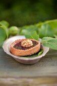 Linzertörtchen (nut and jam tartlet) decorated with a walnut