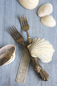 Silver forks, seashells and name tag
