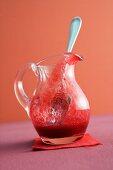 Raspberry sauce in a glass jug