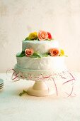 A two-tier wedding cake decorated with marzipan roses