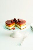 Peach Melba cake with raspberry jelly on a cake stand