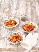 Three portions of rice bake with tomatoes, sausage, pepper, carrots and leek