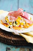 Grain salad with oranges, peppers, courgettes and Parma ham