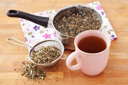 A cup of hempnettle tea and dried tea leaves